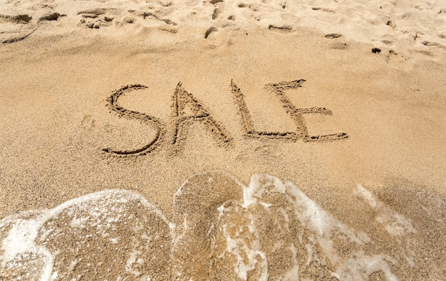 Foto concettuale di vendita scritta sulla spiaggia sabbiosa