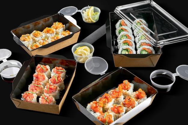 Foto concettuale per la consegna del rotolo di sushi. rotoli in confezioni di cartone su una superficie nera. 3 tipi di involtini piccanti con salmone, scaloppina e tonno, involtini con salmone e cipolle