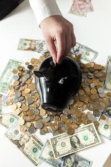 Foto concettuale della donna che inserisce moneta nel salvadanaio