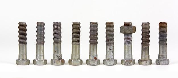 Trama concettuale con nove bulloni con dadi in una riga. un oggetto differisce dal resto in posizione. la parte ha un dado.