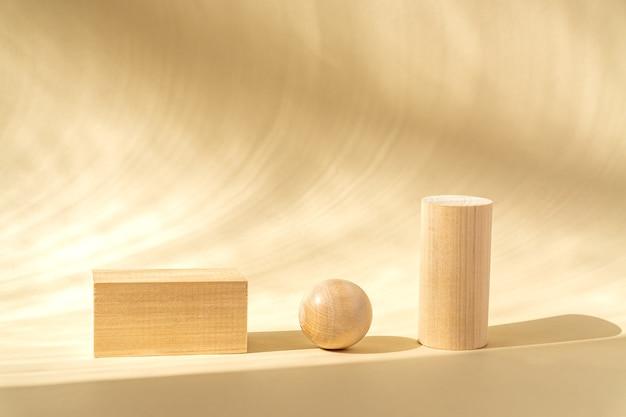 Superficie concettuale con podi in legno chiaro e palla di legno su superficie beige