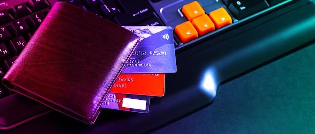 Vista concettuale dello shopping online con carta di credito, portafoglio e laptop.