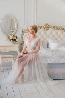 Nozze concettuali, la mattina della sposa in stile europeo. abito da boudoir, tasse nella stanza interna. minimalismo bianco per la sposa
