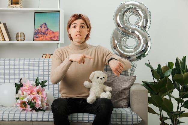 Un bel ragazzo preoccupato per la giornata delle donne felici che tiene in mano l'orsacchiotto punti all'orologio da polso seduto sul divano nel soggiorno