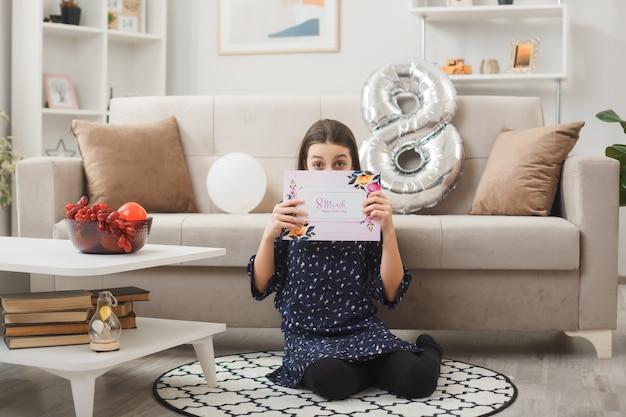 Bambina preoccupata per la festa della donna felice seduta sul pavimento tenendo il viso coperto con una cartolina in soggiorno