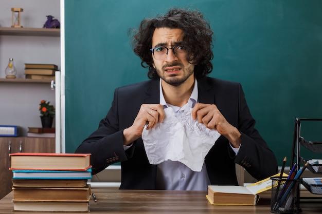 Insegnante maschio interessato che indossa gli occhiali strappa la carta seduta al tavolo con gli strumenti della scuola in classe