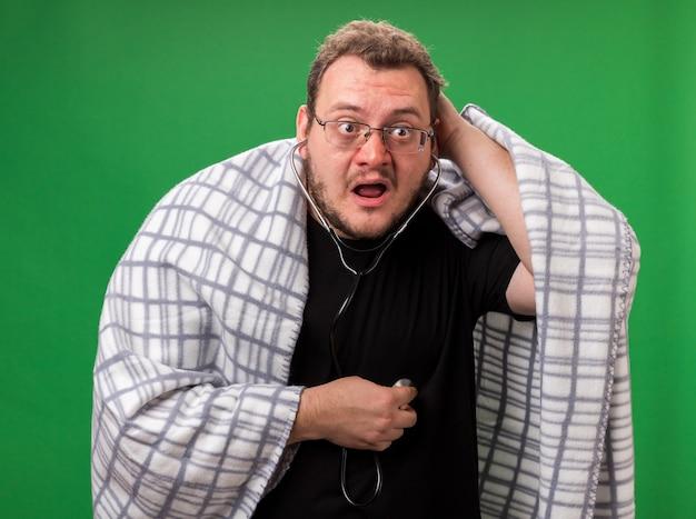 Maschio malato di mezza età preoccupato avvolto in un plaid che ascolta il proprio battito cardiaco mettendo la mano sulla testa