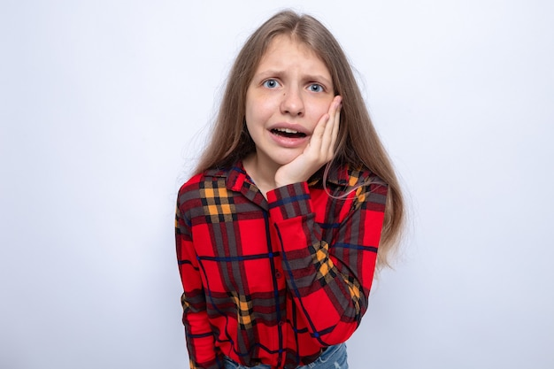 Preoccupato per mettere la mano sulla guancia bella bambina che indossa una camicia rossa isolata sul muro bianco