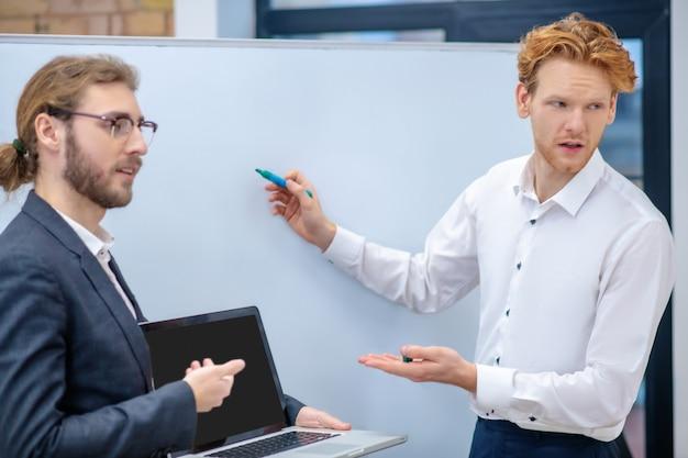 Uomo dai capelli rossi interessato in camicia bianca con pennarello e collega in bicchieri tenendo il portatile in piedi vicino al supporto