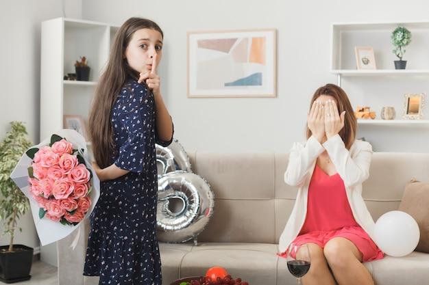 Preoccupata per mostrare il gesto del silenzio, la bambina dà il bouquet alla madre sul divano durante la felice festa della donna in soggiorno