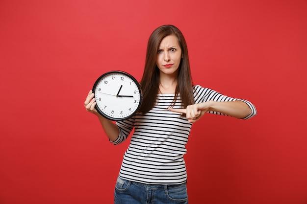 Giovane donna rigorosa interessata che punta il dito indice sull'orologio rotondo in mano isolato su sfondo rosso brillante della parete. il tempo sta finendo. persone sincere emozioni, concetto di stile di vita. mock up copia spazio.