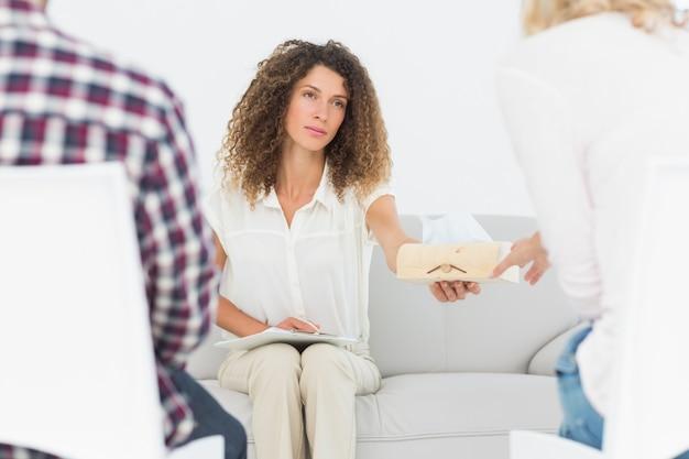 Terapista interessato che passa un tessuto alla donna alla terapia di coppia