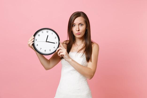 Donna preoccupata in abito bianco con sveglia rotonda