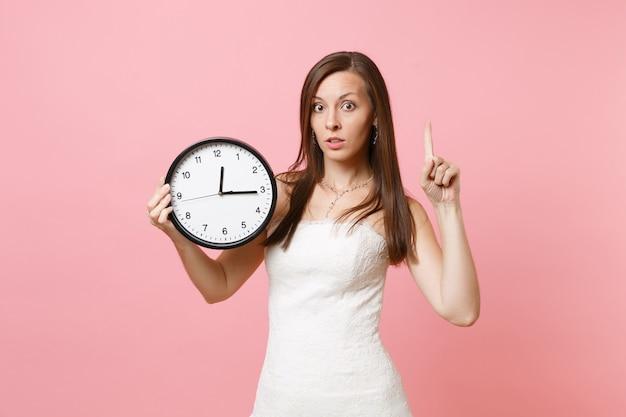 Donna preoccupata in abito bianco che punta il dito indice verso l'alto tenendo la sveglia rotonda