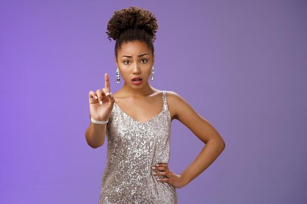 La giovane donna afroamericana preoccupata preoccupata in abito alla moda estende nervosamente il dito indice guarda la telecamera che zittisce vietando di dire a chiunque un segreto accigliato impaurito, dicendo tabù, sfondo blu.