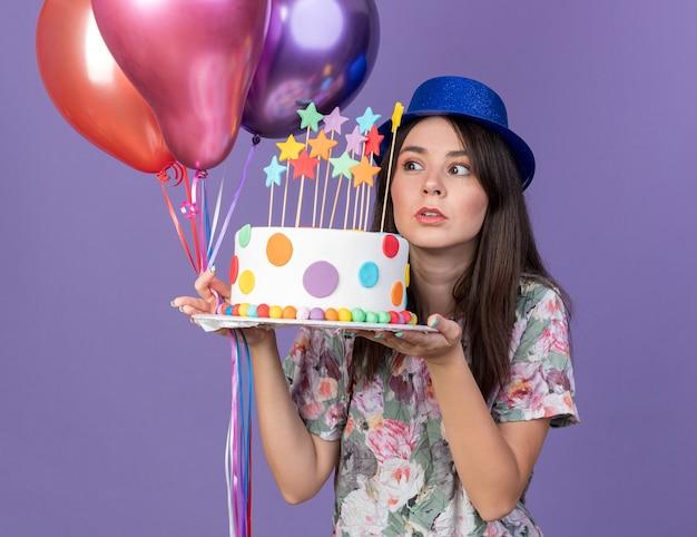 Preoccupato per la giovane bella ragazza che indossa un cappello da festa che tiene e guarda i palloncini con la torta isolata sulla parete blu
