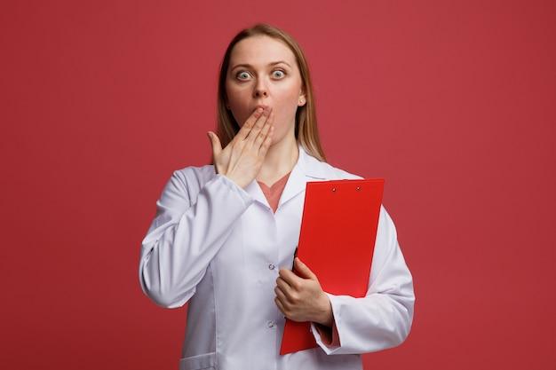 Giovane medico femminile biondo interessato che porta appunti medici della tenuta dell'abito che fa il gesto di oops