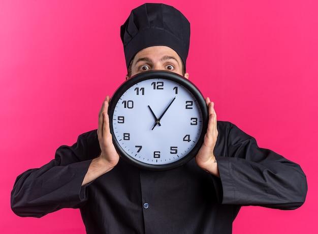 Cuoco maschio giovane biondo interessato in uniforme da chef e berretto che tiene l'orologio guardando la telecamera da dietro isolato su parete rosa