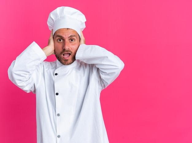 Preoccupato giovane maschio caucasico cuoco in uniforme da chef e berretto guardando la telecamera che copre le orecchie con le mani isolate sulla parete rosa con spazio copia