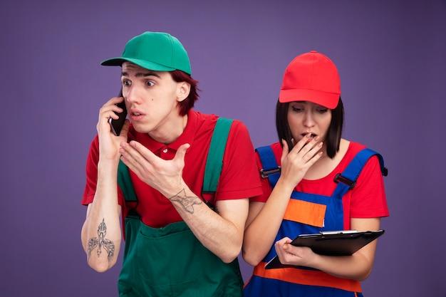 Giovane coppia interessata in uniforme dell'operaio edile e ragazzo del berretto che parla sul telefono che mostra la mano vuota che esamina la ragazza del lato che tiene e che esamina la lavagna per appunti che tiene la mano sulla bocca isolata