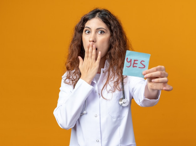 Giovane dottoressa preoccupata che indossa accappatoio medico e stetoscopio che allunga sì nota verso la copertura della bocca con la mano isolata sulla parete arancione con spazio di copia