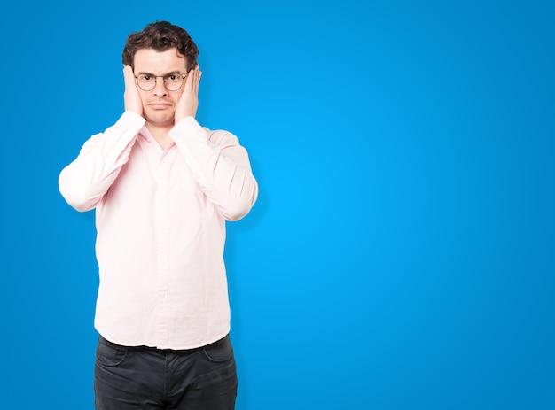 Giovane preoccupato preoccupato per i rumori forti e per coprirsi le orecchie