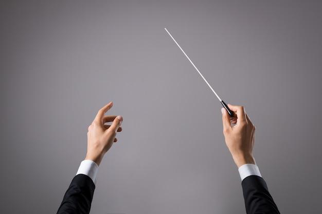 Mano del conduttore di concerto con la bacchetta isolata su grey