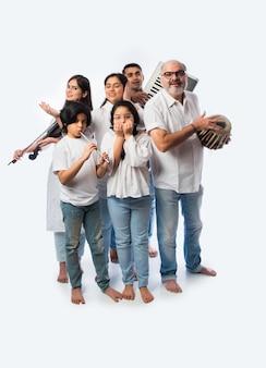 Concerto di una famiglia indiana di sei persone che suonano strumenti musicali in un gruppo e una signora anziana che canta, in piedi su sfondo bianco