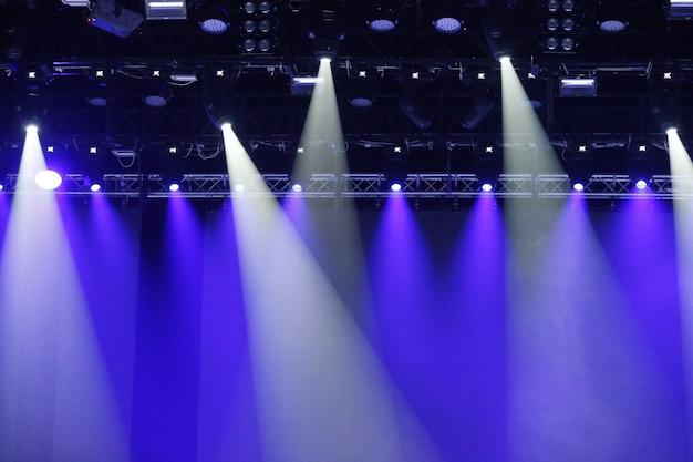 Faretti da concerto. raggi blu e bianchi di potenti proiettori sul palco
