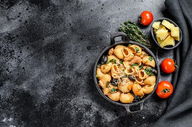 Conchiglie rigate puttanesca con acciughe, pomodori, aglio e olive nere su fondo nero. vista dall'alto. copia spazio