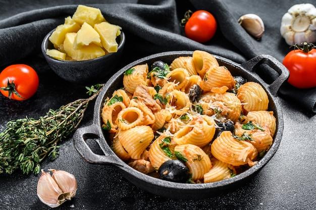 Conchiglie rigate puttanesca con acciughe, pomodori, aglio e olive nere su fondo nero. vista dall'alto