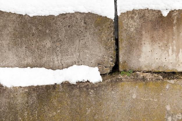 Blocchi di cemento della parte dell'edificio ricoperta di neve bianca, inverno del primo piano