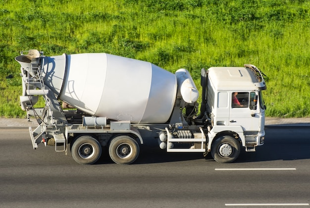 Il camion della betoniera guida l'autostrada stradale.