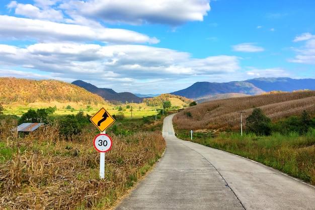 Strada cementata con il segnale stradale e la vista naturale a pai, tailandia.