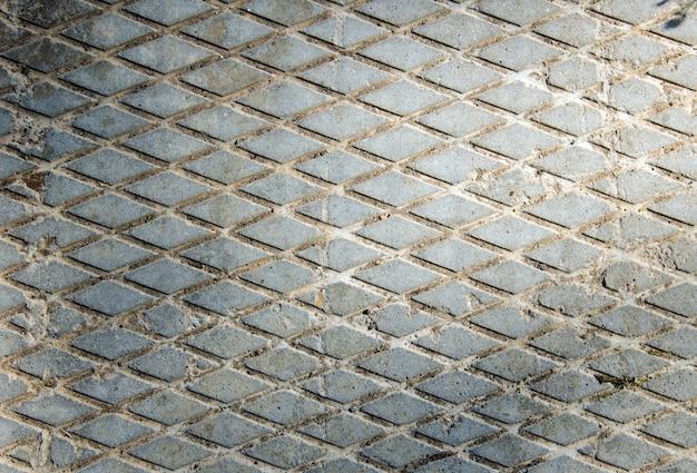 Lastra di cemento. disegno di diamanti. la trama della lastra di cemento. sfondo grigio.