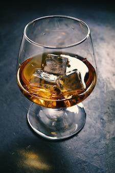 Tavolo in cemento, ghiaccio freddo, cubetti di ghiaccio, whisky bourbon, whisky scotch, bicchierino