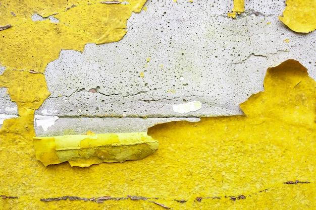 Muro di cemento con canarino giallo, arancione peeling vernice vecchia incrinata danneggiata ruvida trama sfondo luminoso