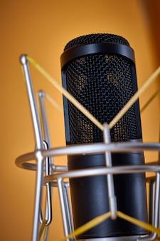 Microfono da studio a condensatore per comunicazioni broadcast, su un supporto da tavolo su sfondo arancione - primo piano