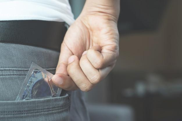 Preservativo pronto per l'uso in tasca pantaloni jeans, offre un concetto di sesso sicuro sul letto previene l'infezione e i contraccettivi controllano il tasso di natalità o la profilassi sicura. giornata mondiale contro l'aids,