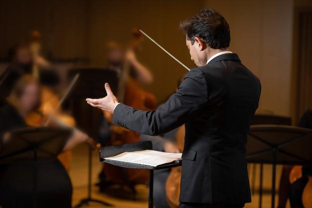 Direttore di orchestra sinfonica con artisti sullo sfondo di una sala da concerto