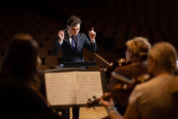 Direttore di orchestra sinfonica con artisti sullo sfondo di una sala da concerto Foto Premium