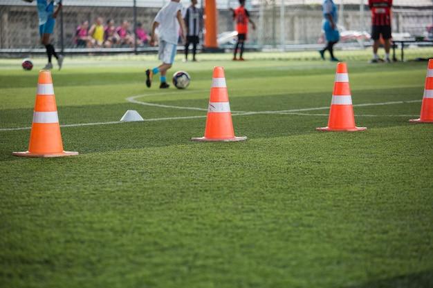 Cono arancione per campo in erba allenamento bambini in accademia di calcio