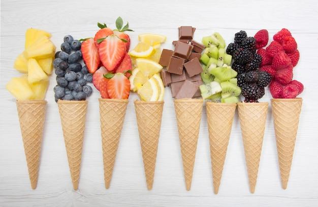 Cialda di cono con frutta fresca e cioccolato, produzione di gelato artigianale Foto Premium