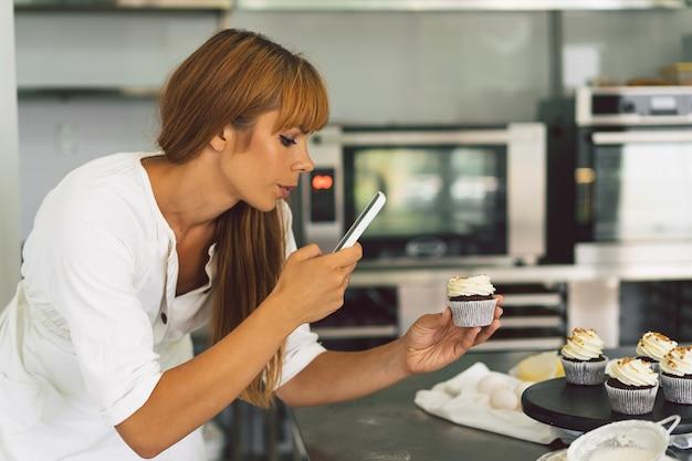 La ragazza pasticcera che fotografa cupcake per la sua ragazza del blog fa una foto di cupcakes su uno smartphone