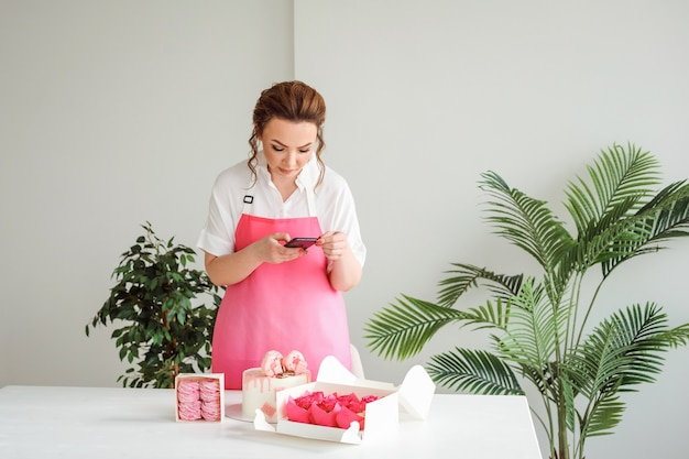 La pasticciera sta scattando foto al suo food blogger di dolci di pasticceria che crea contenuti