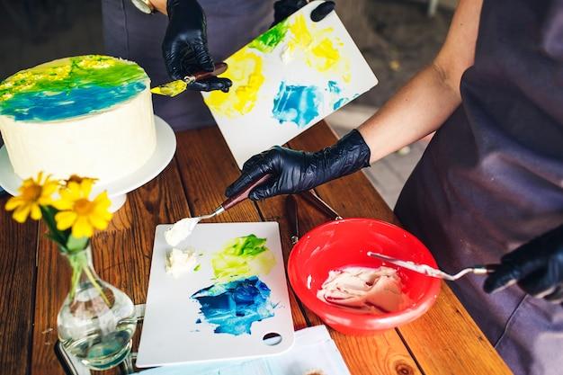 I pasticceri decorano la torta con crema colorata