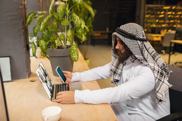 Conferenza. uomo d'affari arabo che lavora in ufficio, centro affari utilizzando dispositivo, gadget. stile di vita saudita moderno. l'uomo in abiti tradizionali e sciarpa sembra sicuro, impegnato, bello. etnia, finanza.