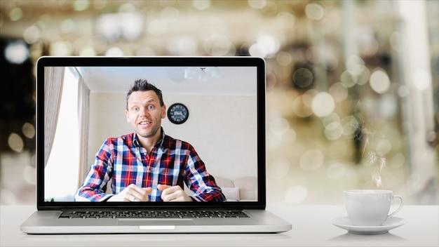Teleconferenza seduti a casa davanti al computer con una tazza di caffè