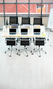 Tavolo da lavoro della sala riunioni per conferenze nell'ufficio dell'azienda pieno di computer portatili notebook tazze di caffè caldo nero e documenti di documenti di dati di relazione e sedie nere con spazio di copia sul pavimento di legno.
