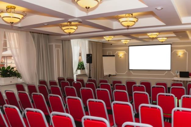 Sala conferenze con sedie rosse, illuminazione interna e schermo isolato bianco vuoto. riunioni di lavoro, conferenze, corsi di formazione, utilizzati come modello per un design elegante. interno della sala conferenze